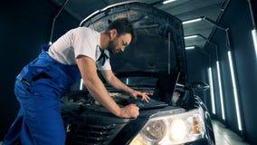 Ο αρσενικός μηχανικός καθορίζει ένα αυτοκίνητο με τη βοήθεια ενός υπολογιστή απόθεμα βίντεο