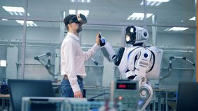 Ο αρσενικός μηχανικός και το ρομποτικό humanoid δίνουν σε μεταξύ τους υψηλός-πέντε φιλμ μικρού μήκους