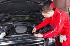 Ο αρσενικός μηχανικός μηχανών πρόκειται να ελέγξει το επίπεδο πετρελαίου σε ένα αυτοκίνητο Στοκ Εικόνα