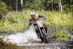 Ο αρσενικός μοτοσυκλετιστής οδηγά το ποδήλατό του μέσω μιας λακκούβας της λάσπης στο δάσος Στοκ Φωτογραφίες