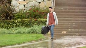 Ο αρσενικός μουσικός κιθαριστών περπατά κάτω από την πορεία στη βροχή απόθεμα βίντεο