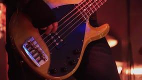 Ο αρσενικός μουσικός στο μαύρο σακάκι δέρματος παίζει τη βαθιά κιθάρα στη σκηνή στη συναυλία φιλμ μικρού μήκους