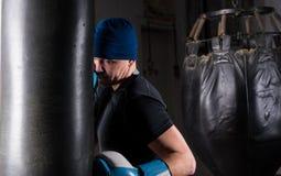 Ο αρσενικός μπόξερ με την πρύμνη κοιτάζει σε ένα καπέλο και εγκιβωτίζοντας γάντια εκπαιδευτικός το W Στοκ Φωτογραφίες