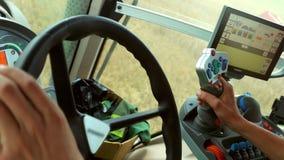 Ο αρσενικός οδηγός της Farmer χεριών στο τιμόνι συνδυάζει τη συγκομιδή στο γεωργικό τομέα Άποψη από μέσα από τις στροφές οδηγών τ απόθεμα βίντεο