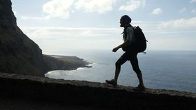 Ο αρσενικός οδοιπόρος με το σακίδιο πλάτης περπατά στην άκρη ενός δρόμου στα Κανάρια νησιά υψηλά επάνω από τον ωκεανό απόθεμα βίντεο