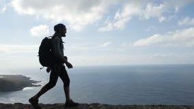 Ο αρσενικός οδοιπόρος με το backpach περπατά στην άκρη ενός δρόμου στα Κανάρια νησιά επάνω από τον ωκεανό φιλμ μικρού μήκους