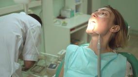 Ο αρσενικός οδοντίατρος μεταχειρίζεται ένα δόντι του όμορφου θηλυκού ασθενή στην οδοντική κλινική χρησιμοποιώντας τον ειδικό εξοπ απόθεμα βίντεο