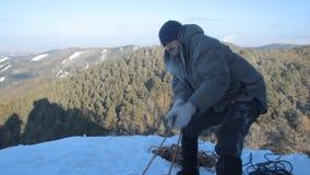 Ο αρσενικός ορειβάτης προετοιμάζει τον εξοπλισμό πρίν αναρριχείται απόθεμα βίντεο