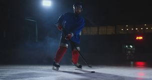 Ο αρσενικός παίκτης χόκεϋ με μια σφαίρα στο χώρο πάγου παρουσιάζει την κίνηση ροής άμεσα στη κάμερα και κοίταγμα άμεσα φιλμ μικρού μήκους
