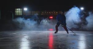 Ο αρσενικός παίκτης χόκεϋ με μια σφαίρα στο χώρο πάγου παρουσιάζει την κίνηση ροής άμεσα στη κάμερα και κοίταγμα άμεσα απόθεμα βίντεο