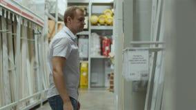 Ο αρσενικός πελάτης επιλέγει τα αγαθά στο κατάστημα των οικοδομικών υλικών φιλμ μικρού μήκους