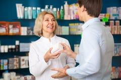 Ο αρσενικός πελάτης συσκέπτεται με το φαρμακοποιό Στοκ Φωτογραφίες