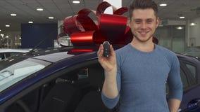 Ο αρσενικός πελάτης θέτει κοντά στο αυτοκίνητο στην αίθουσα εκθέσεως φιλμ μικρού μήκους