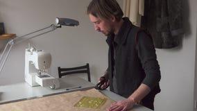 Ο αρσενικός ράφτης με το ψαλίδι κόβει το σχέδιο ιματισμού εγγράφου στο εργαστήριο απόθεμα βίντεο