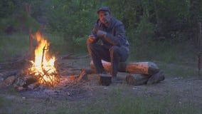 Ο αρσενικός ταξιδιώτης τρώει από το δοχείο κοντά στην πυρκαγιά το βράδυ απόθεμα βίντεο