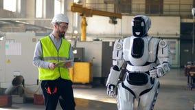 Ο αρσενικός τεχνικός πλοηγεί ένα droid περπατήματος απόθεμα βίντεο