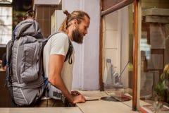 Ο αρσενικός τουρίστας αγοράζει ένα εισιτήριο στον τελικό μετρητή εισιτηρίων σταθμών στοκ εικόνες