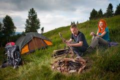 Ο αρσενικός τουρίστας στο λόφο ρίχνει το ξύλο στην πυρά προσκόπων Στοκ Εικόνες