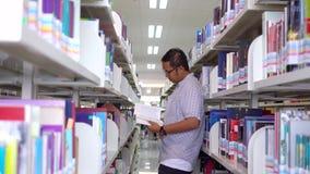 Ο αρσενικός φοιτητής πανεπιστημίου διαβάζει το βιβλίο στο διάδρομο βιβλιοθηκών φιλμ μικρού μήκους