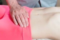Ο αρσενικός χειρωνακτικός σπλαγχνικός μασέρ θεραπόντων θεραπεύει έναν νέο θηλυκό ασθενή Εξωτερική θέρμανση της μήτρας με την ενέρ στοκ εικόνες