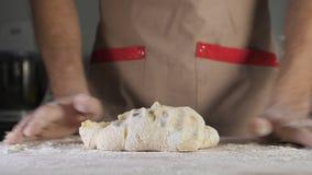 Ο αρτοποιός αρχιμαγείρων ζυμώνει τη ζύμη με το αλεύρι στον πίνακα απόθεμα βίντεο