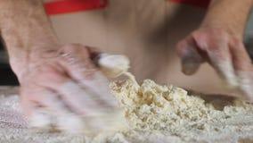 Ο αρτοποιός αρχιμαγείρων ζυμώνει τη ζύμη με το αλεύρι με το χέρι στον πίνακα απόθεμα βίντεο