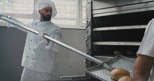 Ο αρτοποιός κινηματογραφήσεων σε πρώτο πλάνο έβγαλε το ψωμί ψησίματος από το φούρνο και εκφορτωμένος στα ράφια χρησιμοποιώντας έν απόθεμα βίντεο