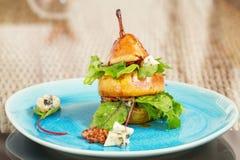 Ο αρχικός τρόπος να εξυπηρετηθεί η σαλάτα αχλαδιών με πράσινο βγάζει φύλλα, μπλε τυρί α Στοκ φωτογραφία με δικαίωμα ελεύθερης χρήσης