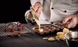 Ο αρχιμάγειρας ή η πιό chocolatier έκχυση λείωσε την άσπρη σοκολάτα στοκ εικόνα με δικαίωμα ελεύθερης χρήσης