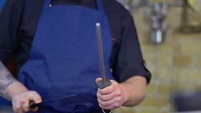 Ο αρχιμάγειρας ακονίζει το μαχαίρι απόθεμα βίντεο