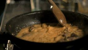 Ο αρχιμάγειρας ανακατώνει το κρέας στο τηγάνισμα του τηγανιού, που μαγειρεύει το φιλέτο Στρογγάνοφ στη σάλτσα απόθεμα βίντεο
