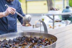 Ο αρχιμάγειρας βάζει τα μύδια Καλό μεσημεριανό γεύμα ή γεύμα Ζήστε υγιή τρόφιμα Κινηματογράφηση σε πρώτο πλάνο ενός δύτη στο χέρι Στοκ Εικόνα