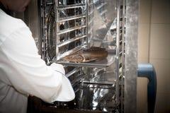 Ο αρχιμάγειρας βάζει το τηγάνι με τα ψάρια στο φούρνο Εκλεκτική εστίαση SH στοκ φωτογραφία με δικαίωμα ελεύθερης χρήσης
