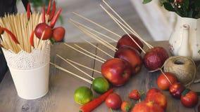 Ο αρχιμάγειρας γυναικών παίρνει το ρόδι από τον ξύλινο πίνακα με τα φρούτα και λαχανικά προετοιμαμένος πρίν μαγειρεύει απόθεμα βίντεο