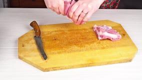 Ο αρχιμάγειρας γυναικών ρίχνει το τεμαχισμένο κρέας σε έναν τέμνοντα πίνακα στην εγχώρια κουζίνα Χέρια που κόβουν το φρέσκο κρέας απόθεμα βίντεο