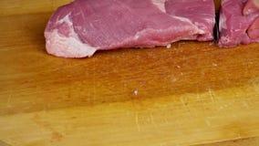 Ο αρχιμάγειρας γυναικών ρίχνει το τεμαχισμένο κρέας σε έναν τέμνοντα πίνακα στην εγχώρια κουζίνα Χέρια που κόβουν το φρέσκο κρέας φιλμ μικρού μήκους