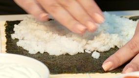 Ο αρχιμάγειρας δίνει να ζυμώσει το ρύζι στο φύλλο nori απόθεμα βίντεο
