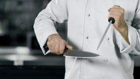 Ο αρχιμάγειρας δίνει το ακονίζοντας μαχαίρι σε σε αργή κίνηση Τρόφιμα μαγείρων χεριών κινηματογραφήσεων σε πρώτο πλάνο στην κουζί απόθεμα βίντεο