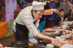 Ο αρχιμάγειρας διανέμει τα συστατικά για την πίτσα, οι συμμετέχοντες της κύριας κατηγορίας στοκ εικόνες
