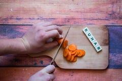Ο αρχιμάγειρας είναι τέμνον καρότο σε έναν ξύλινο τέμνοντα πίνακα με το αιχμηρό knif Στοκ Φωτογραφία