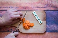 Ο αρχιμάγειρας είναι τέμνον καρότο σε έναν ξύλινο τέμνοντα πίνακα με το αιχμηρό knif Στοκ εικόνες με δικαίωμα ελεύθερης χρήσης