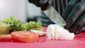 Ο αρχιμάγειρας είναι τέμνον τυρί μοτσαρελών στον τέμνοντα πίνακα κοντά στα λαχανικά απόθεμα βίντεο