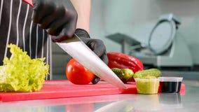 Ο αρχιμάγειρας είναι τέμνουσα ντομάτα για burger, παραδίδει τη μαύρη κινηματογράφηση σε πρώτο πλάνο γαντιών στοκ φωτογραφία