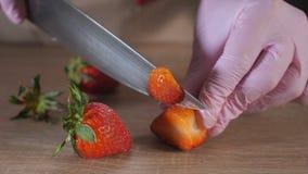Ο αρχιμάγειρας είναι τέμνουσα φράουλα στις φέτες στα λαστιχένια γάντια στον ξύλινο πίνακα απόθεμα βίντεο