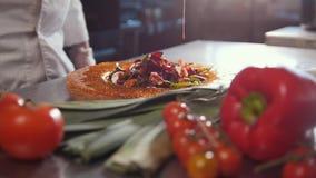 Ο αρχιμάγειρας εξυπηρετεί τη σαλάτα προσθέτοντας τη σάλτσα, φρέσκα λαχανικά στο πρώτο πλάνο απόθεμα βίντεο