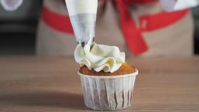Ο αρχιμάγειρας ζύμης διακοσμεί muffin στην άσπρη κρέμα φλυτζανιών εγγράφου με την τσάντα ζύμης φιλμ μικρού μήκους