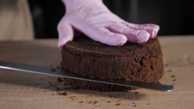 Ο αρχιμάγειρας ζύμης είναι τέμνον κέικ σφουγγαριών σοκολάτας στις φέτες με το μεγάλο μαχαίρι απόθεμα βίντεο