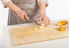 Ο αρχιμάγειρας κόβει μια μπανάνα Στοκ Εικόνα