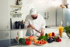 Ο αρχιμάγειρας κόβει τα λαχανικά για να μαγειρεψει το γεύμα Στοκ Εικόνες