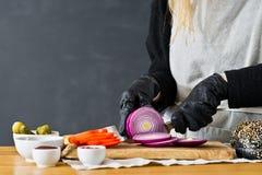 Ο αρχιμάγειρας κόβει τα κόκκινα κρεμμύδια Η έννοια του μαγειρέματος μαύρου Burger Σπιτική συνταγή χάμπουργκερ Κουζίνα, πλάγια όψη στοκ φωτογραφία με δικαίωμα ελεύθερης χρήσης